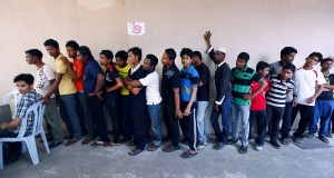 Rohingya men stand in a line at a centre to register for a temporary card issued by UNHCR in Kuala Lumpur